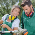 man and woman with lawn mowers